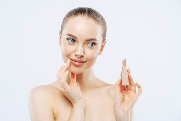Lip care concept. pensive beautiful woman with dark hair, poses with cosmetic product, has minimal makeup, looks sensually aside, poses topless, has well cared body, isolated on white background