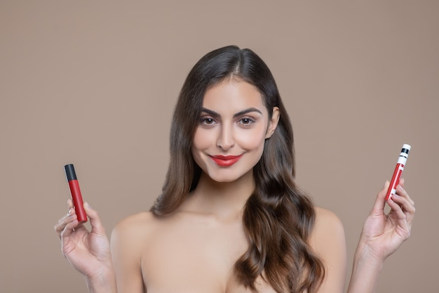 Lip gloss. beautiful young long-haired woman with bare shoulders holding lip glosses in her hands on beige background