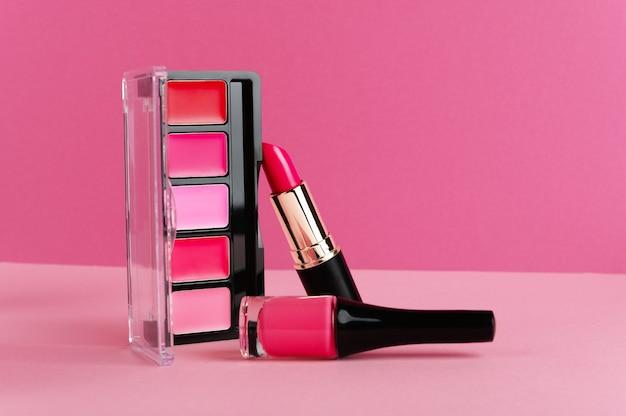 リップグロス、ほお紅パレット、明るいピンクの背景に口紅。