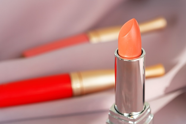 Lip gloss make up products on pink silky cloth