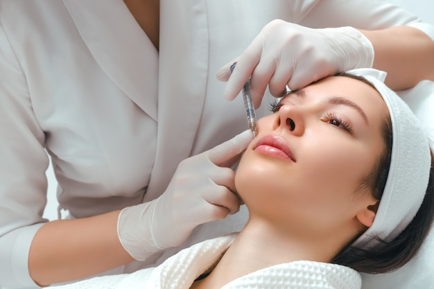 美容院での唇の形の修正手順。専門医は患者の唇に注射をします。唇の増強。