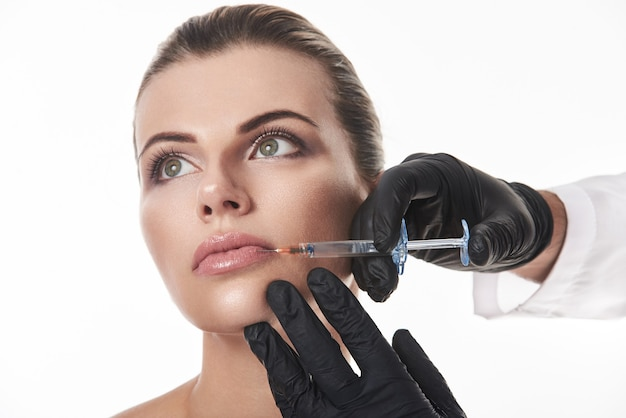 Lips augmentation concept. hands in black gloves making injection of filler to attractive woman's lips