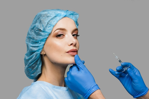 Lips augmentation injections for attractive girl on white surface