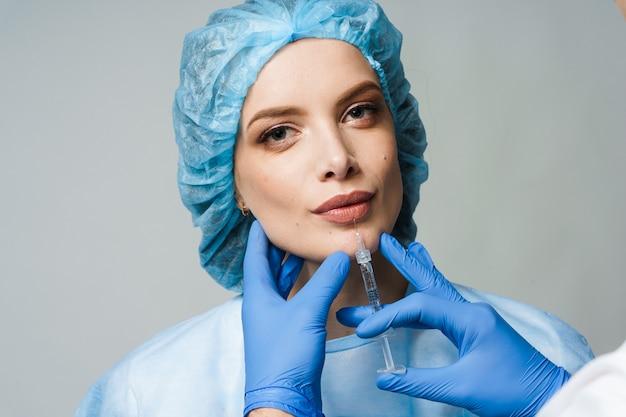 白い表面の魅力的な女の子のための唇増強注射