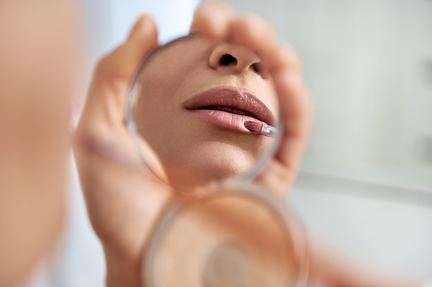 Lips with a lip brush in the small cosmetic mirror.close up. focus on lips. cropped portrait of a woman applying a lipstick with a brush.