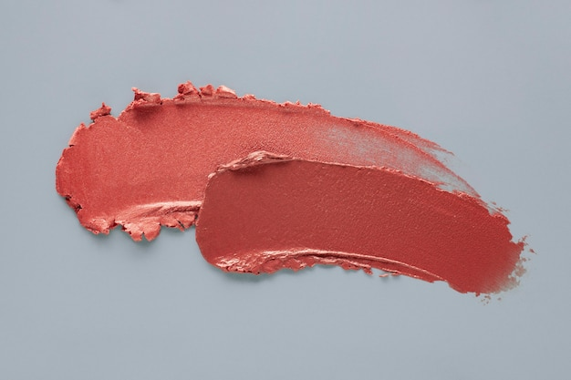 Lipstick burgundy coral smudge swatch on blue gray colored background