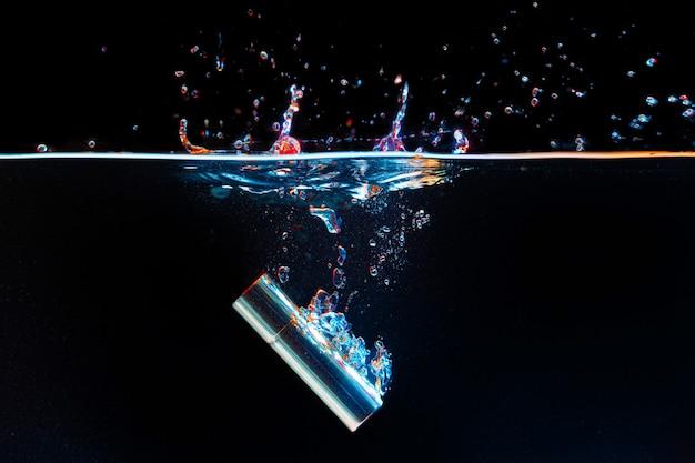 Футляр для помады, падающий в воду с брызгами