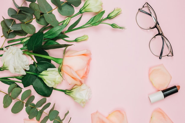 Lipstick; eyeglasses and flower bouquet over pink background