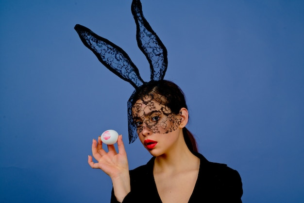 Lipstick kiss print on easter egg. fashion woman in bunny ears with easter egg