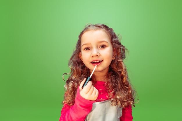Rossetto. bambina che sogna la professione di truccatore. infanzia, pianificazione, educazione e concetto di sogno. vuole diventare impiegato di successo nel settore della moda e dello stile, artista di acconciature.