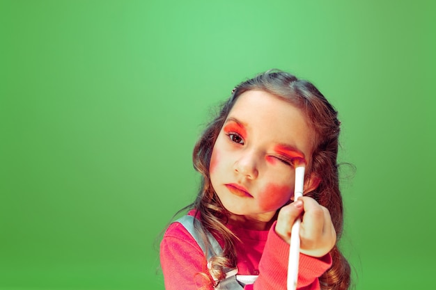 Lipstick. little girl dreaming about profession of makeup artist. childhood, planning, education and dream concept. wants to become successful employee in fashion and style industry, hairstyle artist.