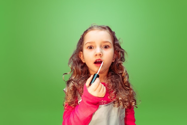 Lipstick. little girl dreaming about profession of makeup artist. childhood, planning, education and dream concept.