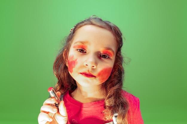 Помада. маленькая девочка мечтает о профессии визажиста. детство, планирование, образование и концепция мечты. хочет стать успешным сотрудником индустрии моды и стиля, стилистом.