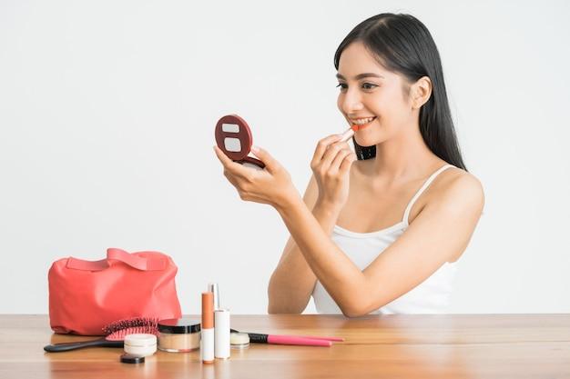 립밤 케어 퍼팅 립스틱 메이크업 여자. 뷰티 아시아 소녀 화장품 준비를 적용하고 행복 미소 거울에 자신을보고. 다민족 아시아 백인 모델.