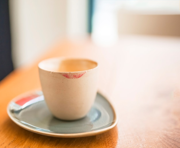 Lipstick mark on coffee cup over the wooden table