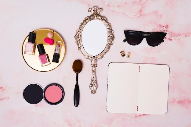 Губная помада; бутылки лака для ногтей; компактная пудра для лица; косметическая кисточка; ручное зеркало; клатчер и открытый дневник на розовом фоне