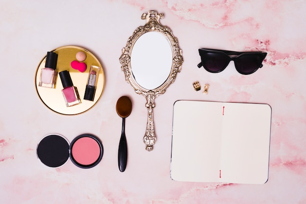 Lipstick; nail polish bottles; compact face powder; makeup brush; hand mirror; clutcher and open blank diary on pink backdrop