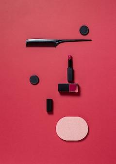 Губная помада, лак для ногтей, расческа и губка на красном фоне. макияж, мириться. косметика.