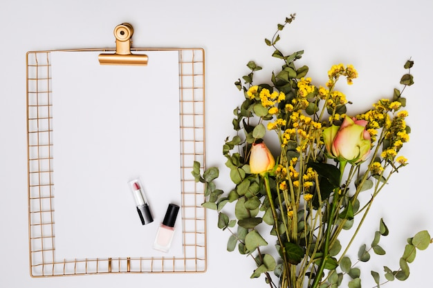 Lipstick; nail varnish on paper over the golden metallic clipboard with flower bouquet isolated on white background