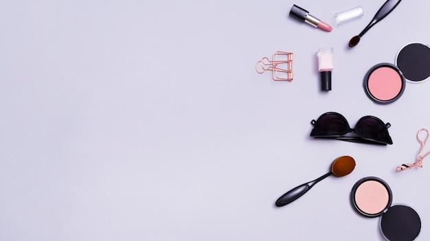 Lipstick; nail varnish; sunglasses; makeup brush; sunglasses; face compact makeup powder on purple background