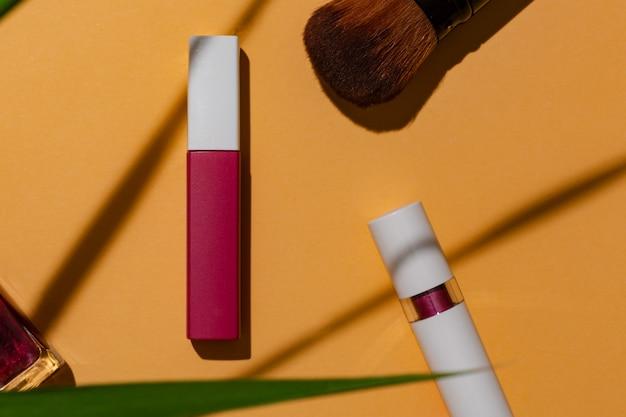 화장품 제품 광고를 위한 단풍 여름 에디션이 있는 주황색 배경의 립스틱