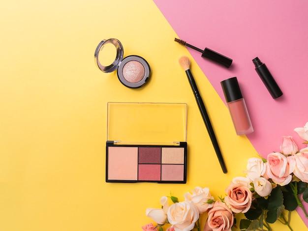 Lipstick, palette, highlight, mascara and brush on yellow