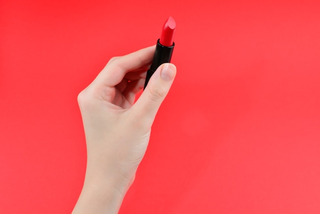 Lipstick swatches on woman hand isolated on red background.