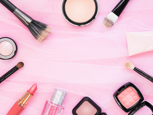 Lipstick, tools, eyeliner, blush, perfume, eye shadow and powder cosmetic in pink theme make up on frame for promotion.
