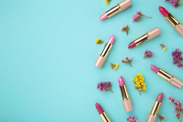 복사 공간 파란색 배경에 아름 다운 꽃과 립스틱