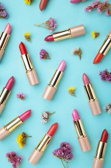 블루 테이블에 아름 다운 꽃과 립스틱