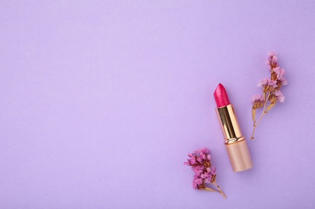 Lipstick with beautiful flowers on purple background with copy space. top view