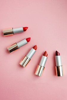 Lipsticks in different shades of pink and red lie. copyspace, top view