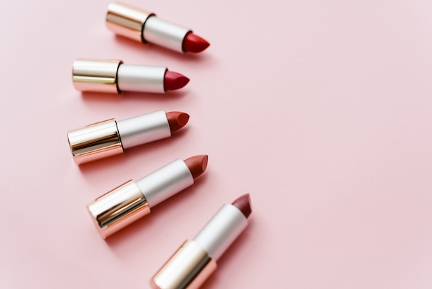 Lipsticks in different shades of pink and red lie on a pastel pink background. copyspace, top view