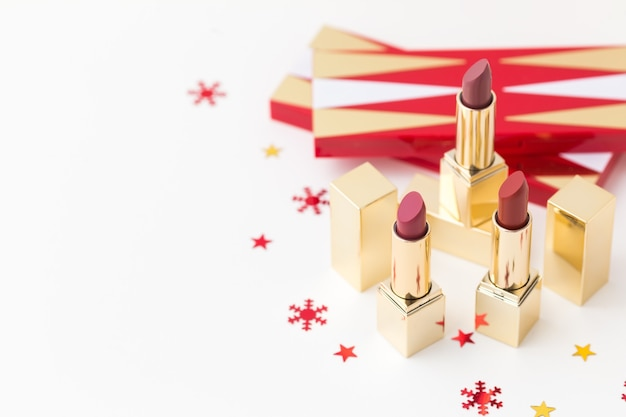 Lipsticks in a gold case and red snowflakes.