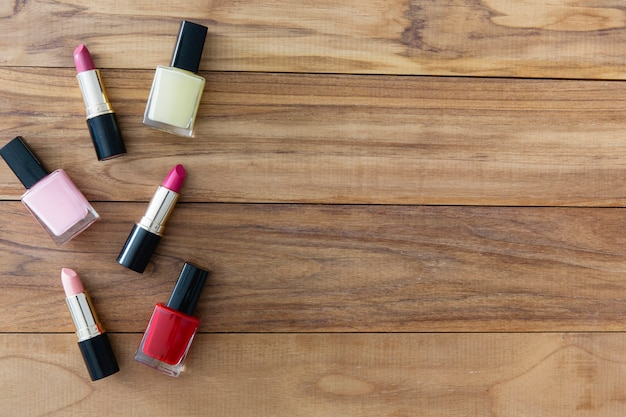Lipsticks and nail polishes on wooden background