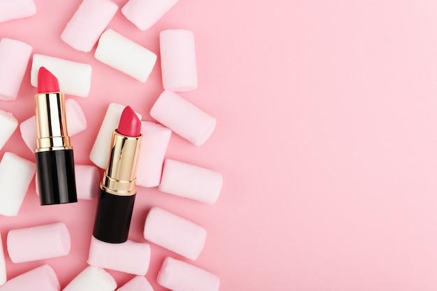 ピンクのパステルカラーの背景の上面図に口紅。