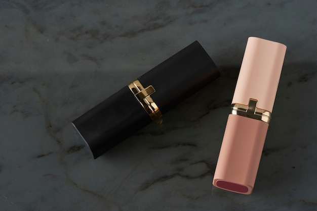 Lipsticks on a smoked glass surface with a marble finish