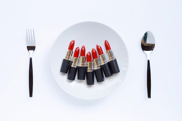 Lipsticks on white dish with fork and spoon on white