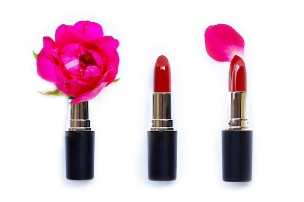 Lipsticks with rose flower on white background.