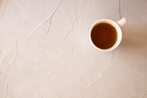 Liquid in ceramic white cup on concrete background