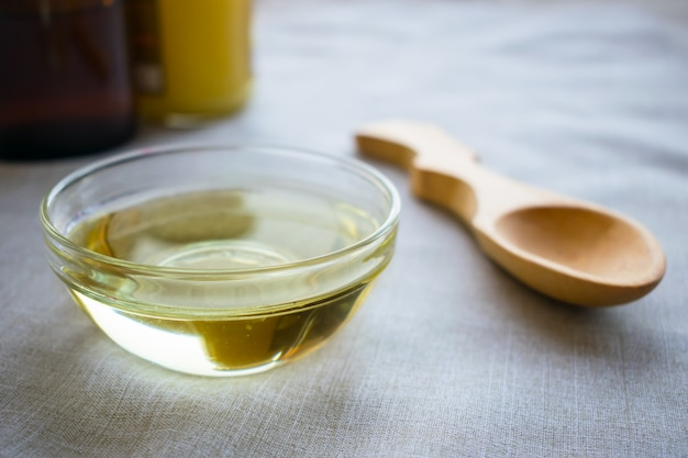 Liquid coconut mct oil in round glass bowl with wooden spoon