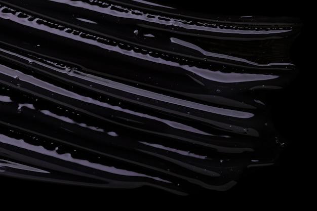 Жидкий косметический гель или сыворотка текстуры размазывают черный фон