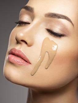리퀴드 화장품 메이크업 파운데이션이 여성 얼굴에 있습니다. 미용 치료 개념. 소녀는 메이크업을합니다.