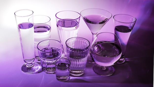 Liquid in different type of glasses on purple background