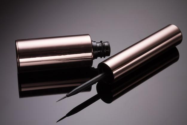 Liquid eyelinder brush on black background