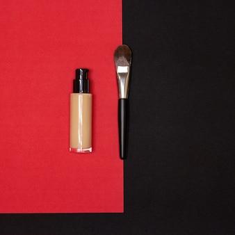 赤と黒の背景に化粧ブラシと液体流体化粧ファンデーションボトル
