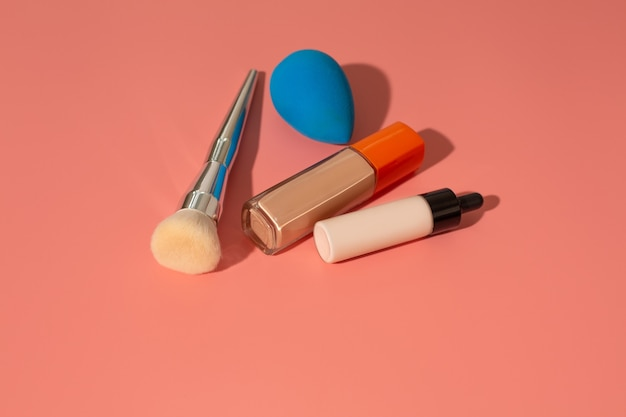 Liquid foundation, adjuster, brush and beauty blender on a pink background