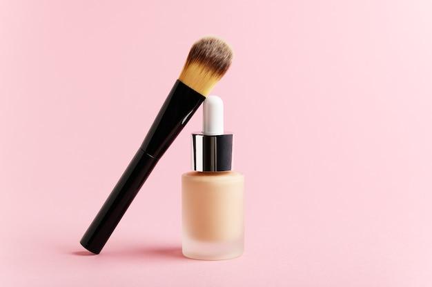 Liquid foundation cream bottle with makeup brush.
