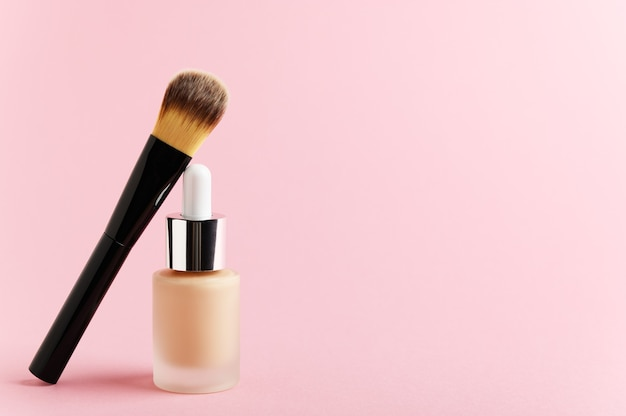 Liquid foundation cream unbranded bottle with makeup brush.