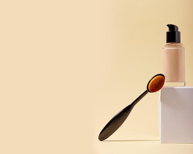스탠드와 화장용 브러시에 있는 병에 담긴 리퀴드 파운데이션. 복사 공간이 있는 베이지색 배경의 얼굴 교정기. 복사 공간이 있는 포장 모형